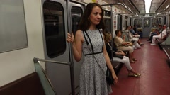 Woman stand back to doors in moving subway car, passenger portrait Stock Footage
