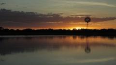 Timelapse sunset lake windmill dingo ducks australia Stock Footage