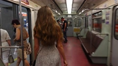 Young woman stand up and come out subway train, POV camera follow after Stock Footage