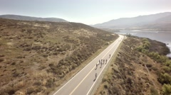 Bike race next to large mountains and river 2 Stock Footage