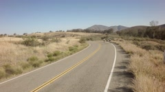 Drone view of bike race on open road with mountains in background 14 Stock Footage