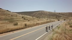 Bicycle race on open road surrounded by mountains and blue sky 4 Stock Footage