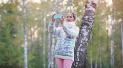 Smiling beautiful woman in a knitted sweater and scarf making selfie with mobile Stock Footage