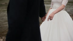 Bride and groom holding hands near the river Stock Footage