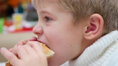 The kid eats a sandwich at a fast food restaurant closeup Stock Footage