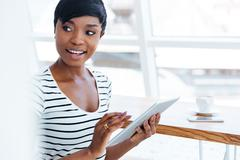 Attractive afro american businesswoman holding tablet computer and looking aw Stock Photos