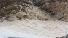 Foam on a rocky ocean shoreline in rough water from storm Stock Footage