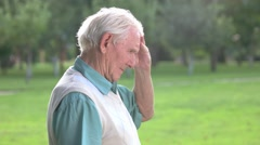Senior man touches his forehead. Stock Footage