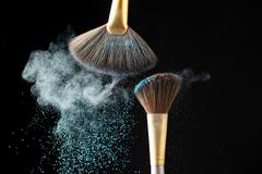 Thick professional brush and loose powder particles scattered around Kuvituskuvat
