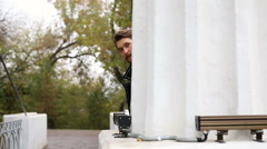 Bearded spy looks out from behind a pillar Stock Footage