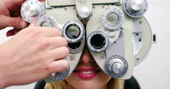 Optometrist examining female patient on phoropter Stock Footage