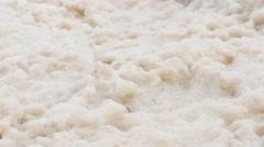 Foam on rocky ocean shoreline in rough water from storm Stock Footage
