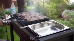 Man pulls meat grills, BBQ braizer Stock Footage