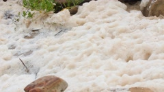 Foam on the ocean shoreline in rough water from storm Stock Footage