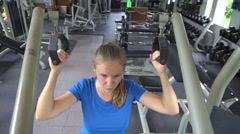 Young woman building arms and shoulders at gym Stock Footage
