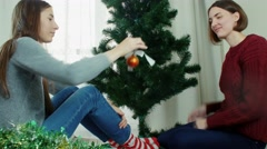 Two young women decorating Christmas tree New year preparation having fun Stock Footage