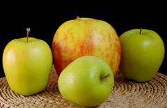 Three green apples and one big apples Stock Photos
