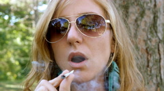 Young blonde woman with sunglasses takes drag from marijuana joint. Stock Footage