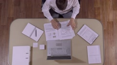 Smart-looking businessman sitting at his table finishes his work Stock Footage