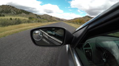 Driving view from side of car mirror mountain valley POV 4K Stock Footage