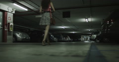 4K Woman walking alone through car park is followed by suspicious male Stock Footage