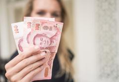 Woman holding cash withdrawned from ATM Stock Photos