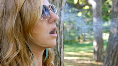 Young blonde woman with sunglasses lights a marijuana joint. Stock Footage