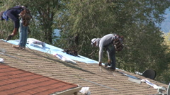 Roofing contractors use nail guns to install shingles on suburban home. Stock Footage