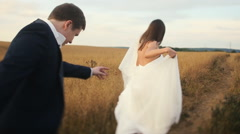 Bride and groom jumping at the wheat field Stock Footage