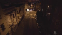 Aerial of skateboarder skating and vehicles moving on city street at night Stock Footage
