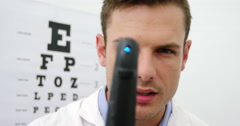Close-up of optometrist looking through ophthalmoscope Stock Footage