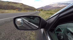 Rear view mirror traffic passing mountain valley POV HD 949 Stock Footage