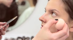 Make-up artist applies concealer on the model's face Stock Footage