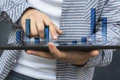 Business person analyzing financial statistics displayed on the tablet screen Stock Photos