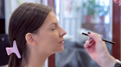 Make-up artist applies eye shadow in the process of working on makeup Stock Footage