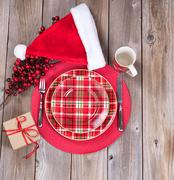Xmas dinner setting with gift box and Santa cap on rustic wooden boards Stock Photos