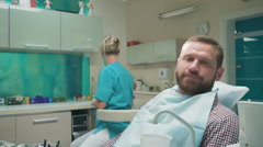Patient rinsing teeth and looking for camera after dental examination. Stock Footage