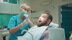 Dentist extracting patient's tooth and looking to camera. Slider shot, right. Stock Footage