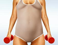 Fatty woman with dumbbells Stock Photos