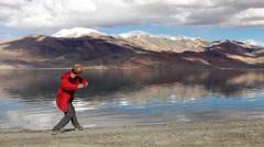 Young teen stone skipping on Tso Moriri lake with the mountain background, Ladak Stock Footage