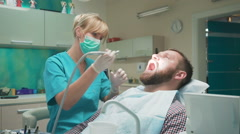 Female dentist drilling tooth of male patient. Stock Footage
