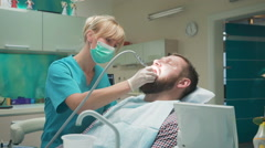 Female dentist drilling tooth of male patient. Slider shot, right. Stock Footage