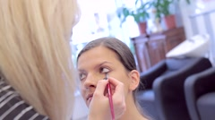 Make-up artist puts a makeup on model eyes Stock Footage