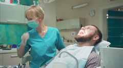 Female dentist drilling tooth of male patient and looking to camera. Slider shot Stock Footage