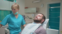Female dentist examining teeth of male patient and looking to camera. Stock Footage
