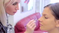 Make-up artist coats eyelids with eye-shadow close-up Stock Footage