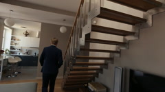 Groom with bouqet rises on the stairs Stock Footage