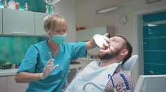 Dentist making an injection of anesthetic into the gums and talking with patient Stock Footage