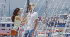 4K Romantic couple share a kiss beside water fountain in the city Stock Footage