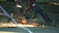 Construction worker cuts metal with a angle grinder on a construction site, slow Stock Footage